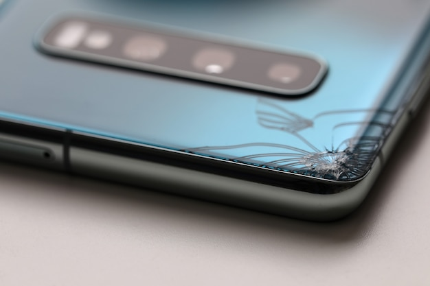 Modern smartphone lying at table with crack in corner close-up