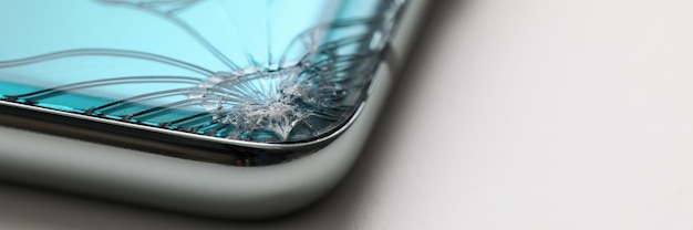 Modern smartphone lying at table with crack in corner