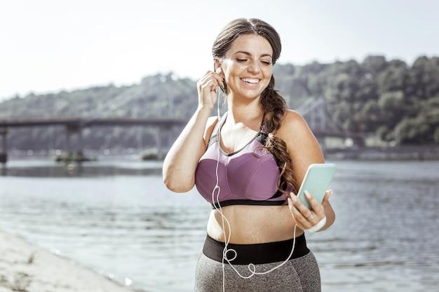 現代のスマートフォン。ヘッドフォンを装着しながらスマートフォンを見ているポジティブな素敵な女性