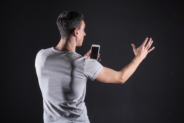 현대 스마트 폰. 손을 뻗고 감각 패널 앞에 서서 휴대 전화를 사용하는 똑똑한 잘 생긴 좋은 남자