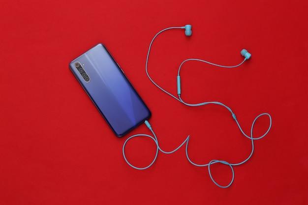 빨간색에 파란색 이어폰과 현대 스마트 폰입니다.