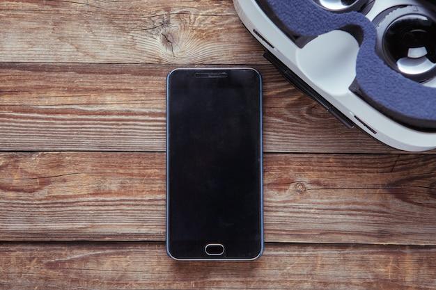 Современный смартфон с пустым экраном и очками виртуальной реальности