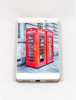 英国ロンドンの象徴的な伝統的な英国の赤い電話ブースのフルスクリーン画像を備えたモダンなスマートフォン