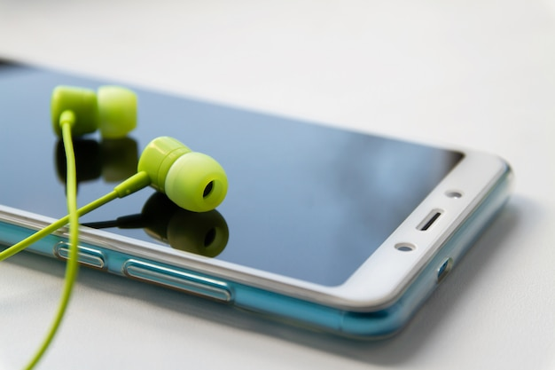 Modern smartphone with lime headphones on light background.