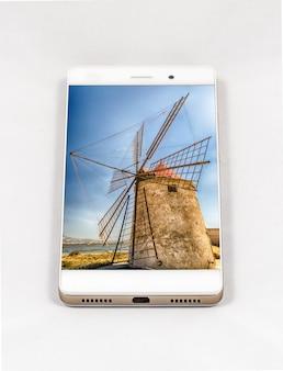イタリアの古い風車の写真と現代のスマートフォン。旅行スマートフォン写真のコンセプト。このコンポジションのすべての画像は私が作成したものであり、ポートフォリオで個別に入手できます。