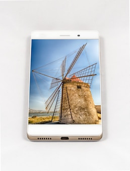 Modern smartphone with picture of an old windmill in italy. concept for travel smartphone photography. all images in this composition are made by me and separately available on my portfolio