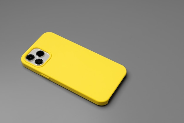 Modern smartphone in yellow case on gray background