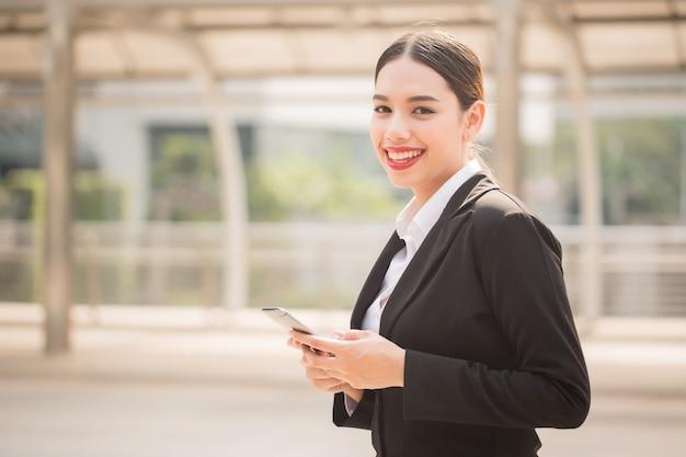 コピースペースでスマートフォンを使用して現代の笑顔の美しいビジネス女性