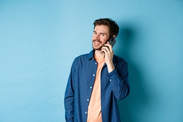 携帯電話で話し、カメラを幸せそうに見て、青い背景の上に立っている現代の笑顔の男。