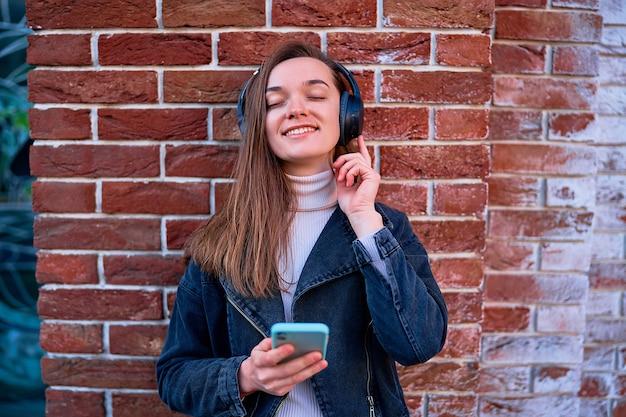 야외에서 음악을 듣기 위해 무선 헤드폰과 스마트 폰을 사용하는 현대 웃는 행복 캐주얼 젊은 여자