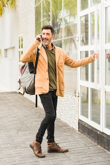 Modern smiling man with his backpack talking on mobile phone while opening the glass door