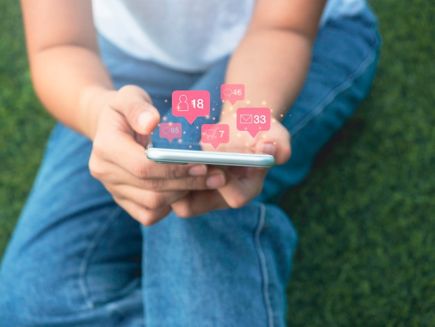 Modern social media icon in pink balloon floating around the smartphone in woman's hands who sitting on green grass with relax gesture, lifestyle, technology and social network concept.
