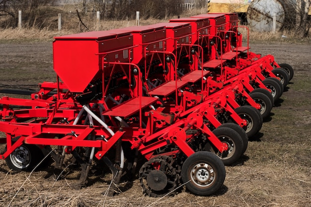 Modern sowing seeds machine. farmer tractor seeding. red combine plow. sowing crops at agricultural fields in spring.
