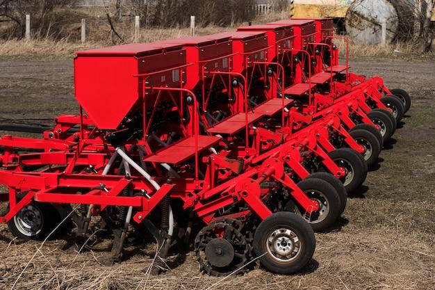 Современная машина для посева семян. крестьянин сеет трактор. красный комбайн плуг. посев на сельскохозяйственных полях весной.