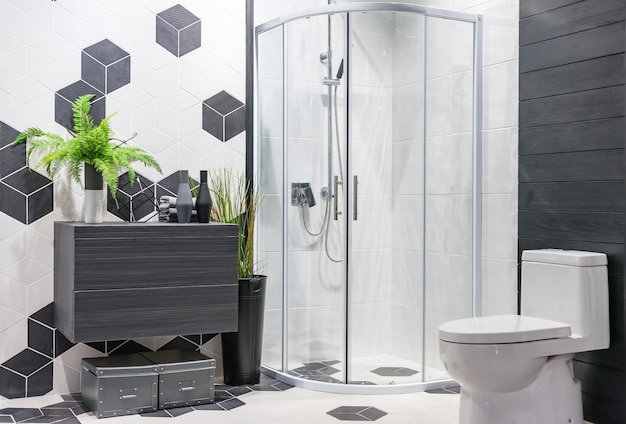 Modern spacious bathroom with bright tiles with glass shower, toilet and sink.