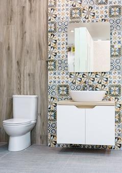 Современная просторная ванная комната с яркими плитами с туалетом и раковиной.