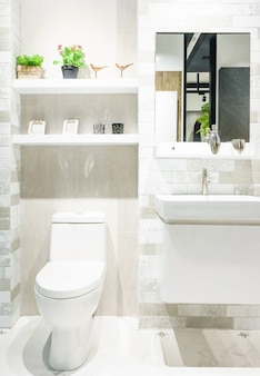Modern spacious bathroom with bright tiles with toilet and sink.