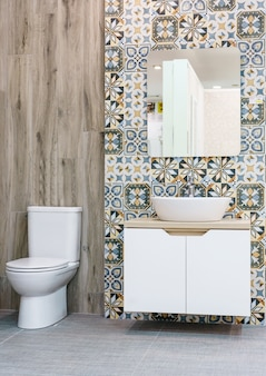 Modern spacious bathroom with bright tiles with toilet and sink
