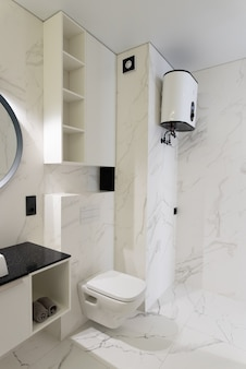 Modern spacious bathroom with marble tiles with a crisp white toilet bathtub and sink side view