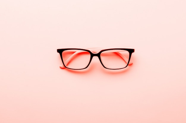 Modern spectacles eye glass isolated on yellow background. trendy living coral color of year 2019. top view.