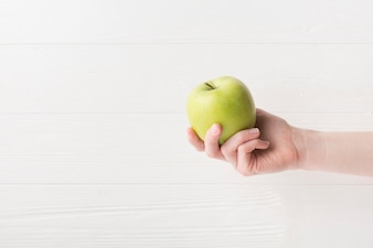 Modern sport composition with hand holding apple