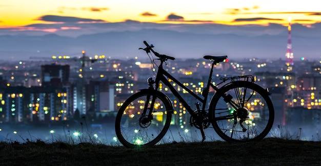 Modern sports city bicycle standing alone over night city background