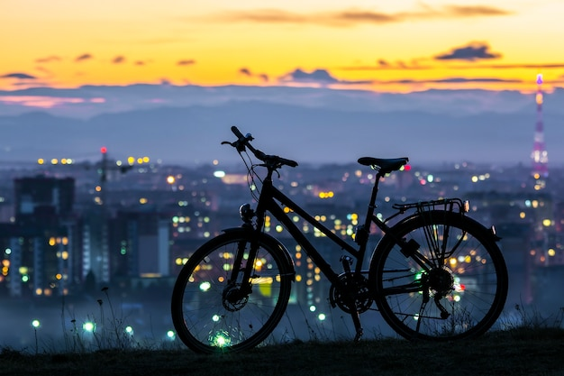 Modern sports city bicycle standing alone over night city scene