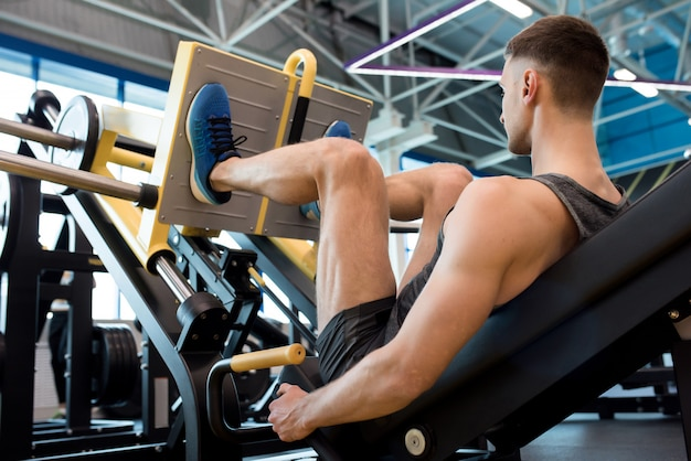 ジムで脚を訓練する現代のスポーツマン