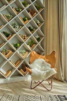 Современный весенний интерьер со встроенным книжным шкафом и кожаным креслом. роскошная гостиная и дизайн интерьера. дневной свет.