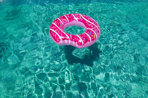 Modern sprinkled donuts inflatable float in sunny pool wall straight down on bright clear pool water summer concept, relax and lifestyle