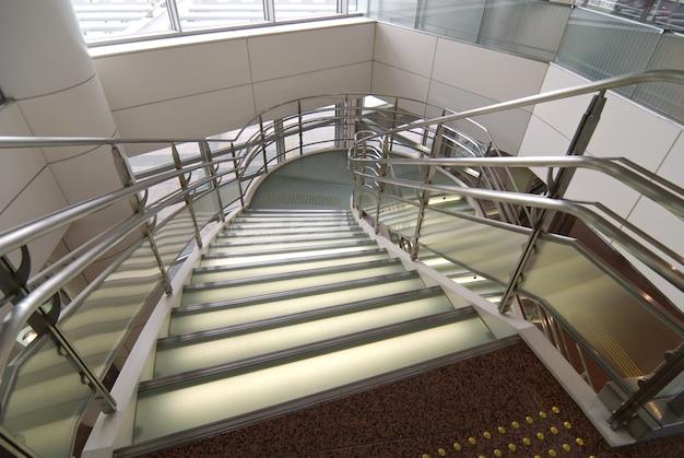 금속 손잡이가 달린 현대적인 스테인드 및 무광택 유리 계단