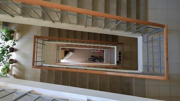 주거용 건물의 현대적인 계단입니다. 관점에서 계단입니다. 회색 세라믹 타일. 갈색 나무 울타리와 콘크리트 계단이 있는 일반적인 계단. 위에서 볼 수 있습니다.