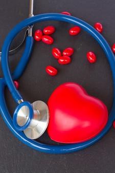 赤いハートと黒い背景に丸薬とモダンな聴診器