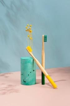 현대 정물입니다.아이소메트릭 대각선 투영입니다. 기하학적 녹색 모양, 스탠드. 대나무 칫솔. 노란색 말린 꽃. 제로 폐기물, 파스텔 블루와 핑크 배경. 친환경적이고 지속 가능한 라이프 스타일