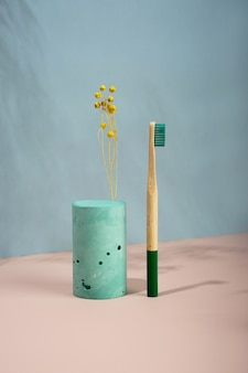 현대 정물입니다.아이소메트릭 대각선 투영입니다. 기하학적 녹색 모양, 스탠드 및 연단.노란색 말린 꽃. 폐기물, 파스텔 파란색 및 분홍색 배경. 친환경적이고 지속 가능한 라이프 스타일.