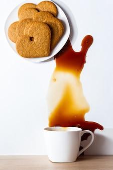 皿にハート型のジンジャーブレッドクッキーを置き、テーブルにコーヒーをこぼした現代の静物画。