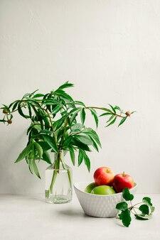 花瓶に花の花束、フルーツボウルに赤と緑のリンゴのある現代の静物。