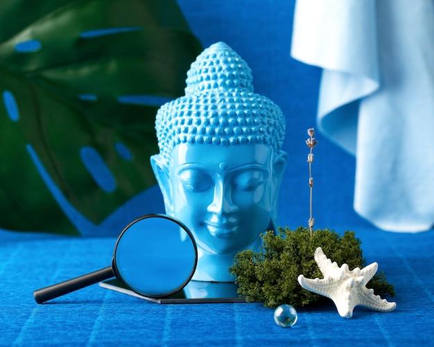 Современный натюрморт с головой будды, пальмовыми листьями, морскими звездами.