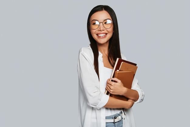 Современный студент. красивая молодая азиатская женщина с книгами и улыбка, стоя на сером фоне