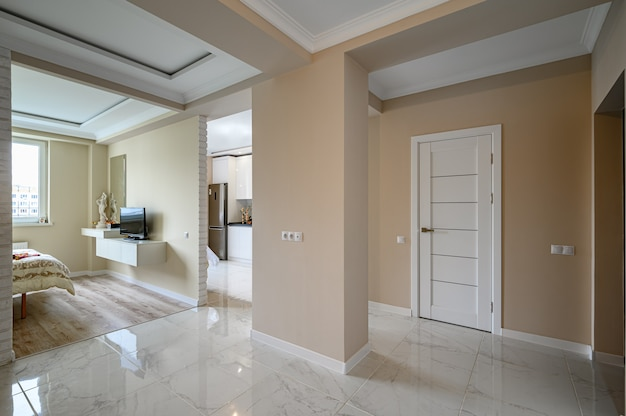 Modern studio partment with white kitchen in classic style and beige bedroom
