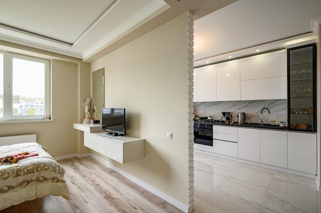 Современная квартира-студия с белой кухней в классическом стиле и бежевой спальней.