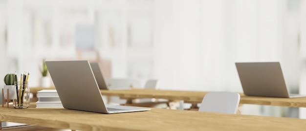 Современный кабинет с ноутбуком на деревянном столе, канцелярские товары и размытый фон
