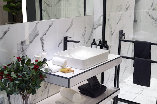 A modern style bathroom with basin in a black and white tone colored.