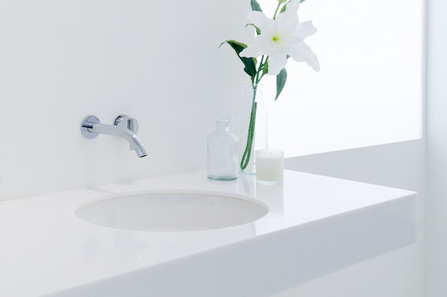 A modern style bathroom with basin in a white colored.