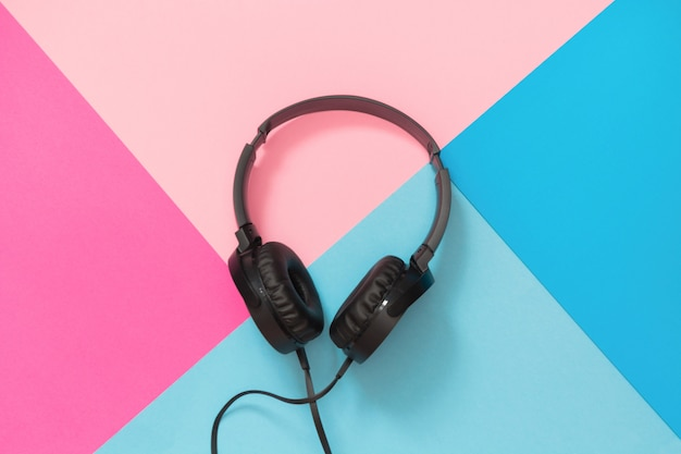 Modern style black headphones on pink blue.