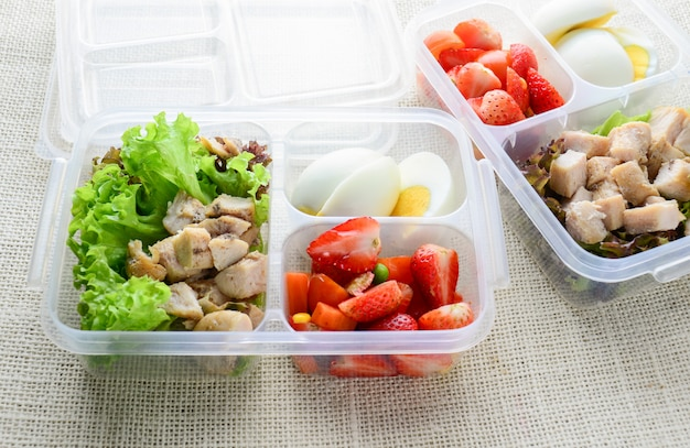 Modern style clean food, boiled egg, grilled chicken and avocado, strawberry, vegetable salad
