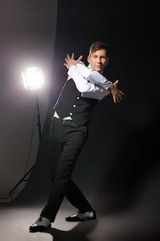 Танцор в современном стиле танцует на темном фоне