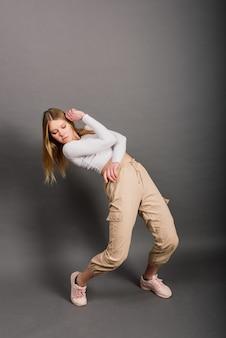 スタジオの背景にポーズをとるモダンなスタイルのダンサー