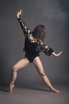 Танцовщица современного стиля позирует на сером фоне студии в тумане