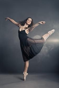 Танцор в современном стиле позирует на сером фоне
